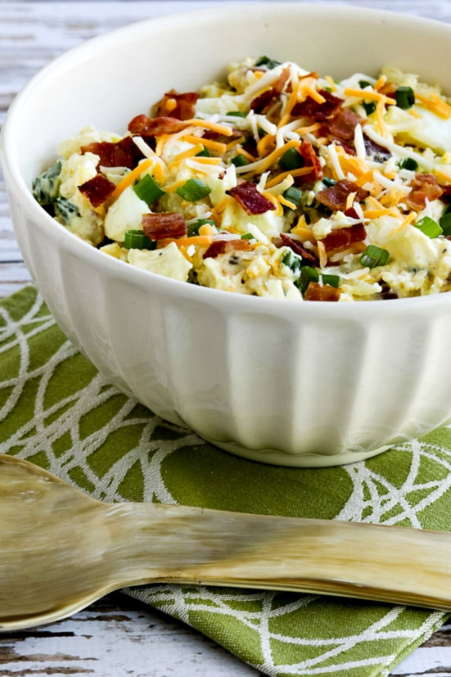 Loaded Cauliflower Mock Potato Salad salad in bowl with serving spoon